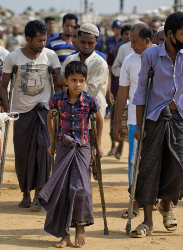 Wounded Rohingya refugees walk with the help of crutches as they await the arrival of a U.N. Security Council team at the Kutupalong Rohingya refugee camp in Kutupalong, Bangladesh, Sunday, April 29, 2018. A U.N. Security Council team visiting Bangladesh promised Sunday to work hard to resolve a crisis involving hundreds of thousands of Rohingya Muslims who have fled to the country to escape military-led violence in Myanmar. (AP/A.M. Ahad)